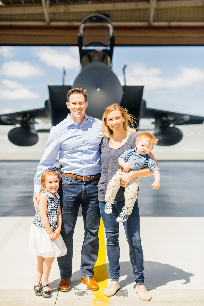 A family stands holding each other close in front of an F-15 at Barnes Air National Guard Base wearing coordinated outfits for these F-15 fighter pilot family photos