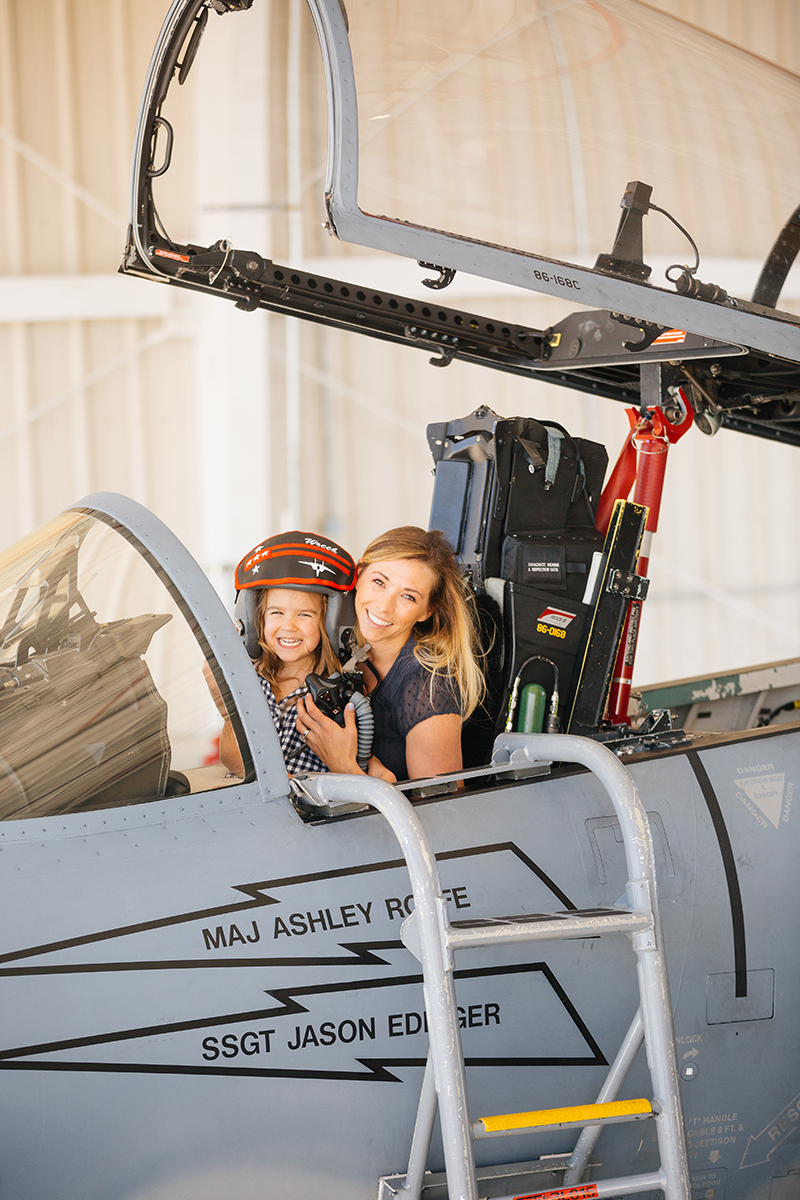 A pilot poses in the cockpit of an F-15 with her daughter sitting on her lap at Barnes Air National Guard Base wearing coordinated outfits for these F-15 fighter pilot family photos