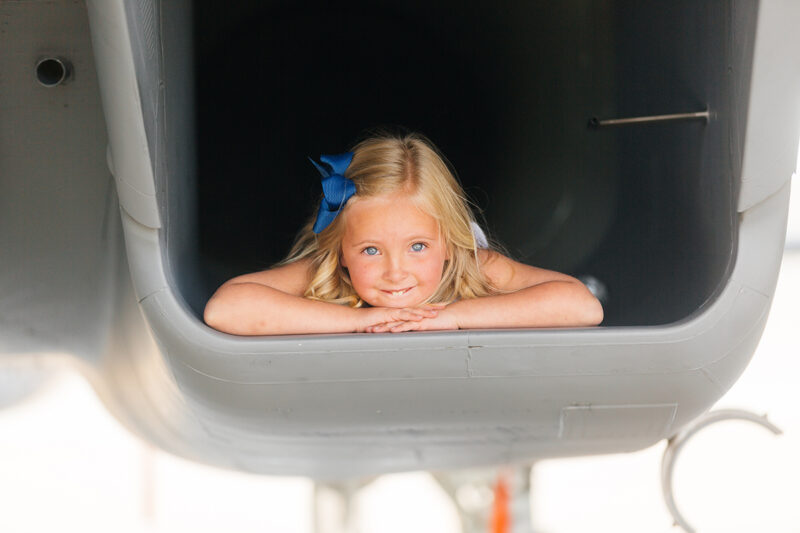 A girl laying down in the intake of an F-15 at Barnes Air National Guard Base wearing a dress for these F-15 fighter pilot family photos