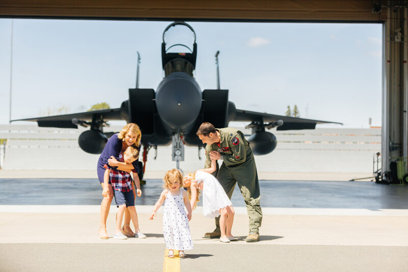 A family stands holding each other close in front of an F-15 fighter at Barnes Air National Guard Base near Boston wearing a flight suit and coordinated outfits for these F-15 fighter pilot family photos