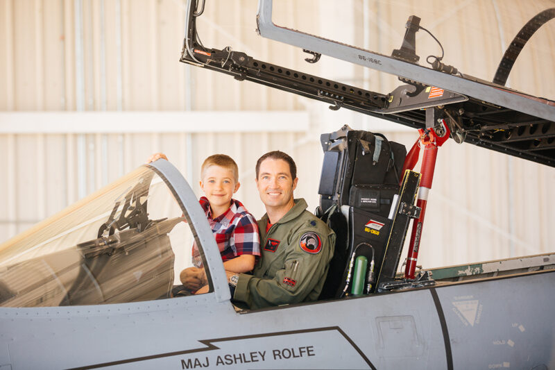 A pilot sits in the cockpit of an F-15 with his son on his lap at Barnes Air National Guard Base wearing a flight suit and a coordinated outfit for these F-15 fighter pilot family photos
