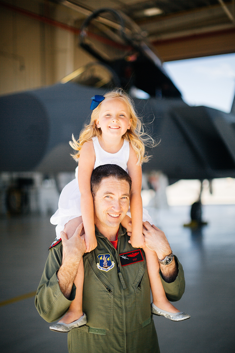 A pilot holds his daughter on his shoulders in front of an F-15 at Barnes Air National Guard Base wearing a flight suit and a coordinated outfit for these F-15 fighter pilot family photos