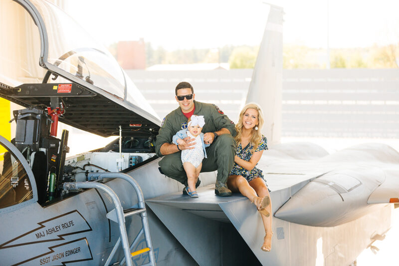 A family sits on the wing of an F-15 at Barnes Air National Guard Base wearing a flight suit and a coordinated outfit for these F-15 fighter pilot family photos