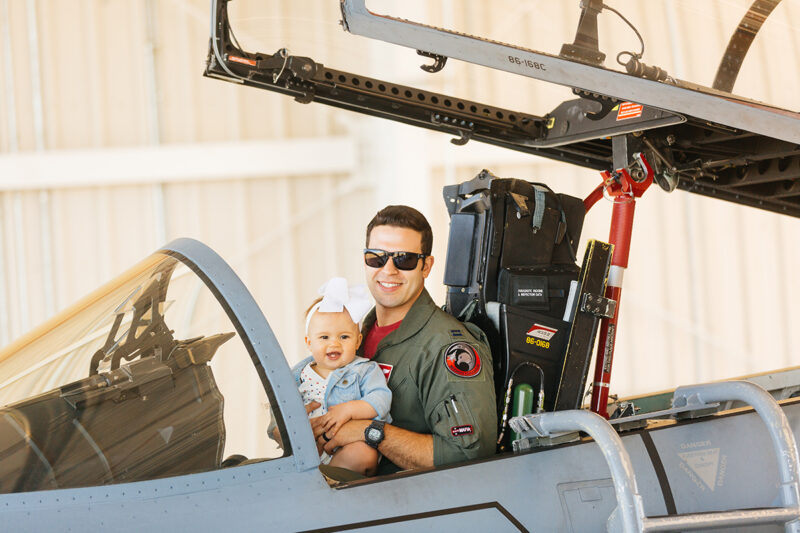 A pilot sits in the cockpit of an F-15 with his daughter on his lap at Barnes Air National Guard Base wearing a flight suit and a coordinated outfit for these F-15 fighter pilot family photos