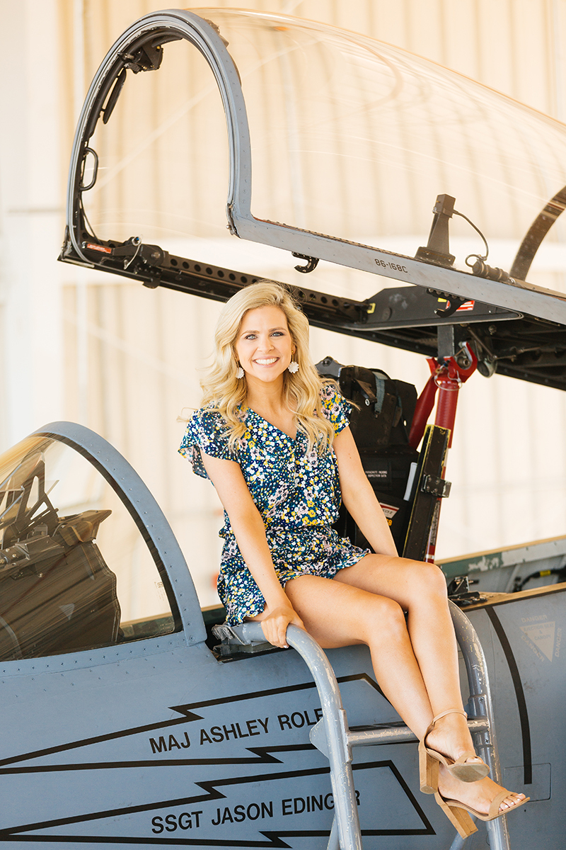 A wife sits on the ladder of the cockpit of an F-15 at Barnes Air National Guard Base wearing a flight suit for these F-15 fighter pilot family photos