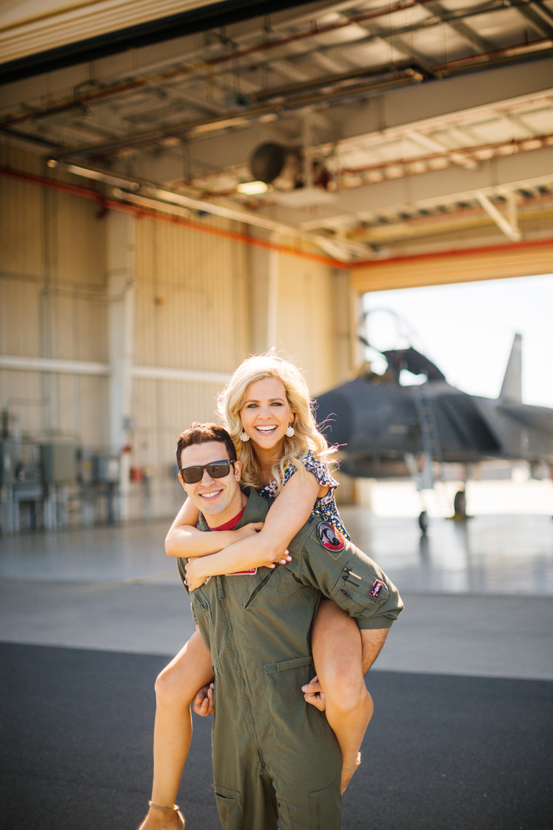 A pilot gives his wife a piggyback ride in front of an F-15 at Barnes Air National Guard Base wearing a flight suit and a coordinated outfit for these F-15 fighter pilot family photos