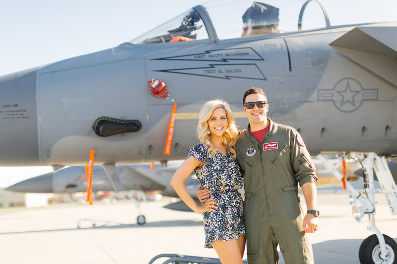 A pilot holds his wife in front of an F-15 at Barnes Air National Guard Base wearing a flight suit and a coordinated outfit for these F-15 fighter pilot family photos
