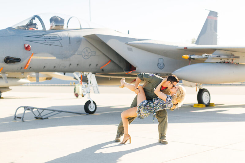A pilot dips his wife and kisses her in front of an F-15 at Barnes Air National Guard Base wearing a flight suit and a coordinated outfit for these F-15 fighter pilot family photos