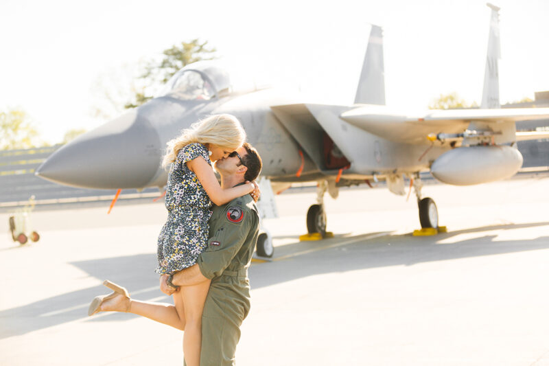A pilot lifts his wife up and kisses her in front of an F-15 at Barnes Air National Guard Base wearing a flight suit and a coordinated outfit for these F-15 fighter pilot family photos
