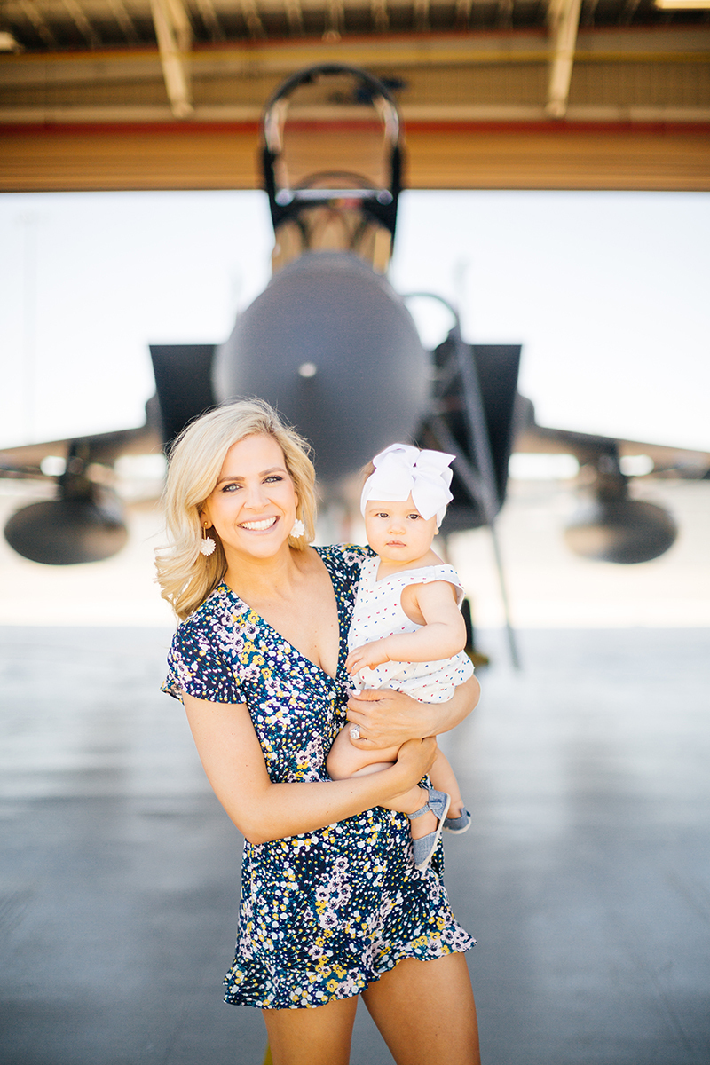 A pilot's wife holds their daughter in front of an F-15 at Barnes Air National Guard Base wearing coordinated outfits for these F-15 fighter pilot family photos