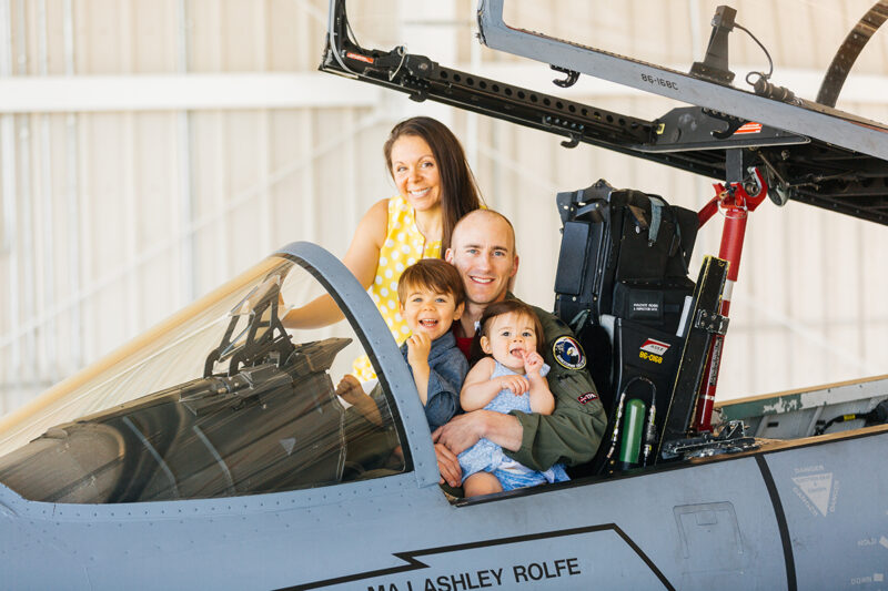 A family sits in the cockpit of an F-15 at Barnes Air National Guard Base near Boston wearing a flight suit and coordinated outfits for these F-15 fighter pilot family photos