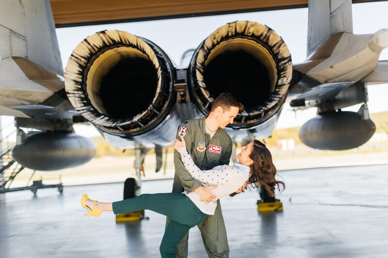 A pilot and his wife stand together as he dips her behind an F-15 at Barnes Air National Guard Base wearing a flight suit and a coordinated outfit for these F-15 fighter pilot family photos