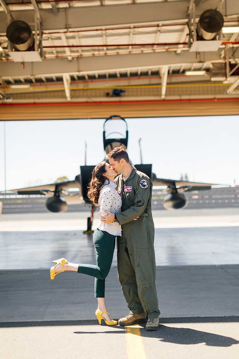 A pilot and his wife stand together kissing in front an F-15 at Barnes Air National Guard Base wearing a flight suit and a coordinated outfit for these F-15 fighter pilot family photos