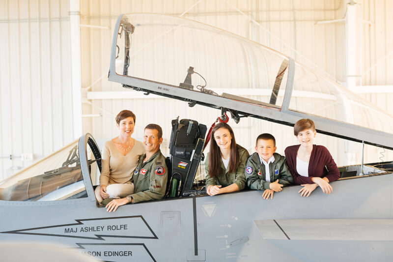 A family sits in the cockpit of an F-15 at Barnes Air National Guard Base wearing a flight suit and coordinated outfits for these F-15 fighter pilot family photos