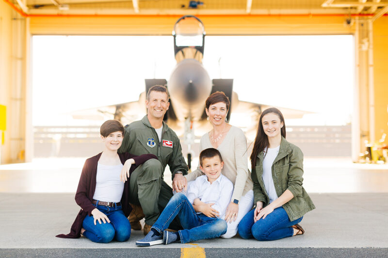 A family sits holding each other close in front of an F-15 at Barnes Air National Guard Base wearing a flight suit and coordinated outfits for these F-15 fighter pilot family photos