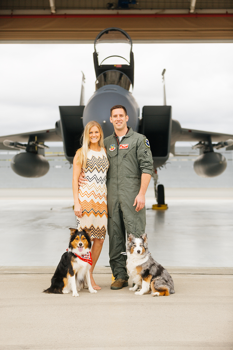 A pilot and his wife stand together with their dogs in front an F-15 at Barnes Air National Guard Base wearing a flight suit and coordinated outfits for these F-15 fighter pilot family photos