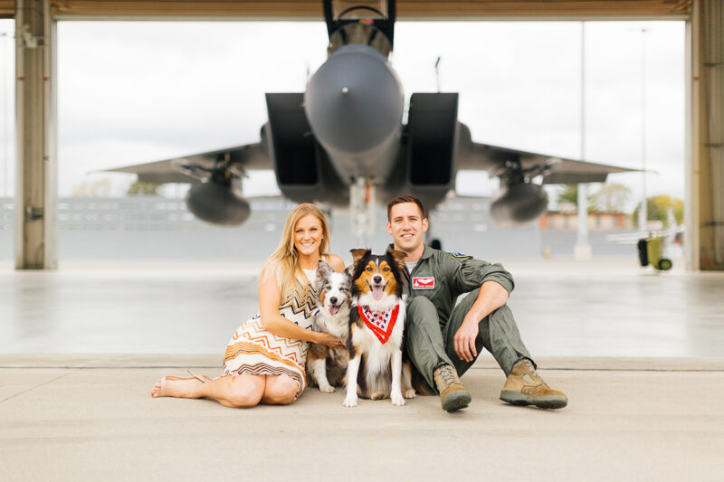 A pilot and his wife sit together with their dogs in front an F-15 at Barnes Air National Guard Base wearing a flight suit and coordinated outfits for these F-15 fighter pilot family photos