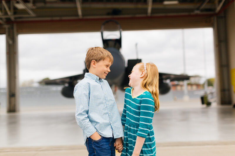 A pilot's children hold hands in front of an F-15 at Barnes Air National Guard Base wearing coordinated outfits for these F-15 fighter pilot family photos