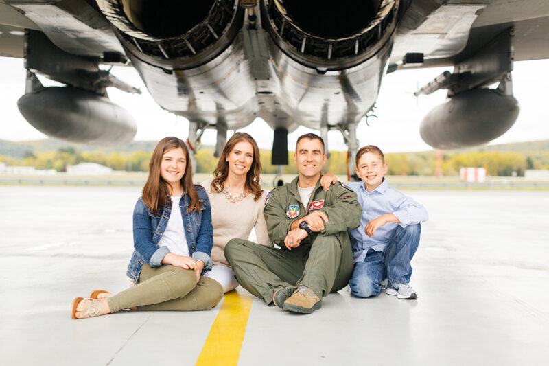 A family sits under an F-15 holding each other close at Barnes Air National Guard Base wearing a flight suit and coordinated outfits for these F-15 fighter pilot family photos