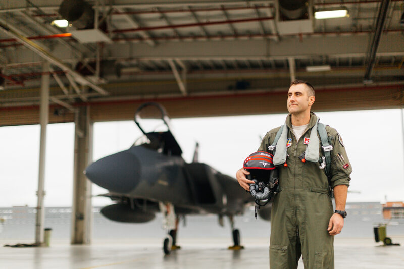 A pilot poses in front of an F-15 at Barnes Air National Guard Base wearing a flight suit for these F-15 fighter pilot family photos