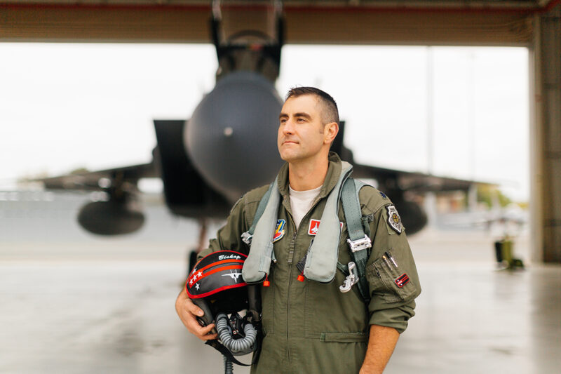 A pilot poses in front of an F-15at Barnes Air National Guard Base wearing a flight suit for these F-15 fighter pilot family photos