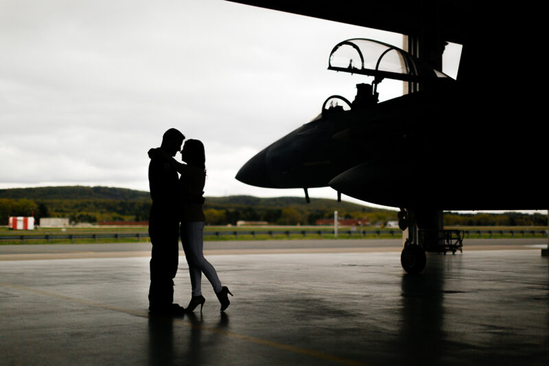A pilot and his wife stand together in front an F-15 at Barnes Air National Guard Base wearing a flight suit and a coordinated outfit for these F-15 fighter pilot family photos