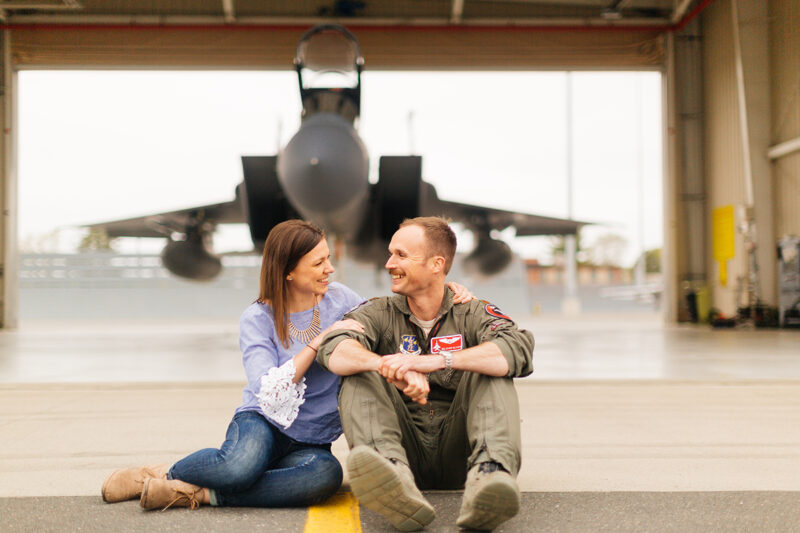 A pilot and his wife sit together in front of an F-15 at Barnes Air National Guard Base wearing a flight suit and a coordinated outfit for these F-15 fighter pilot family photos