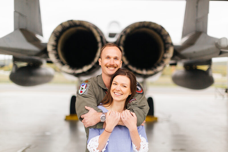 A pilot and his wife stand together behind an F-15 at Barnes Air National Guard Base wearing a flight suit and a coordinated outfit for these F-15 fighter pilot family photos