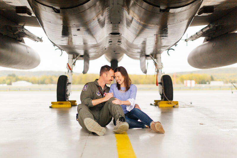 A pilot and his wife sit together under an F-15 at Barnes Air National Guard Base wearing a flight suit and a coordinated outfit for these F-15 fighter pilot family photos