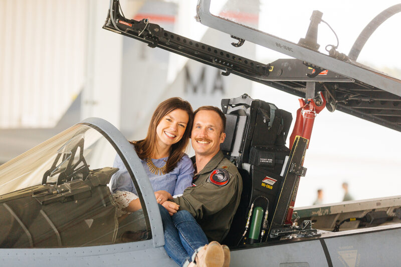 A pilot sits in the cockpit of an F-15 with his wife sitting in his lap at Barnes Air National Guard Base wearing a flight suit and a coordinated outfit for these F-15 fighter pilot family photosA pilot sits in the cockpit of an F-15 fighter with his wife sits in his lap in a hangar at Barnes Air National Guard Base near Boston wearing a flight suit and a coordinated outfit for these F-15 fighter pilot family photos