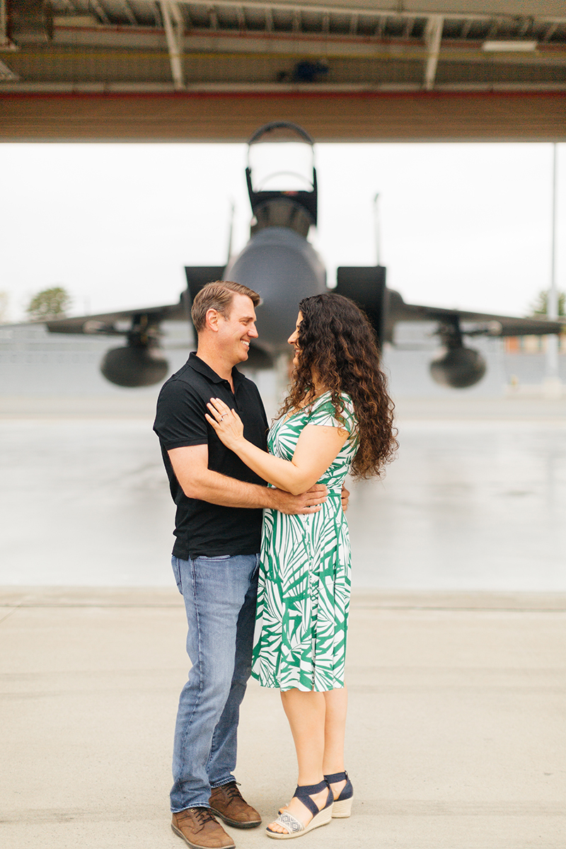 A pilot and his wife stand together in front an F-15 at Barnes Air National Guard Base wearing coordinated outfits for these F-15 fighter pilot family photos