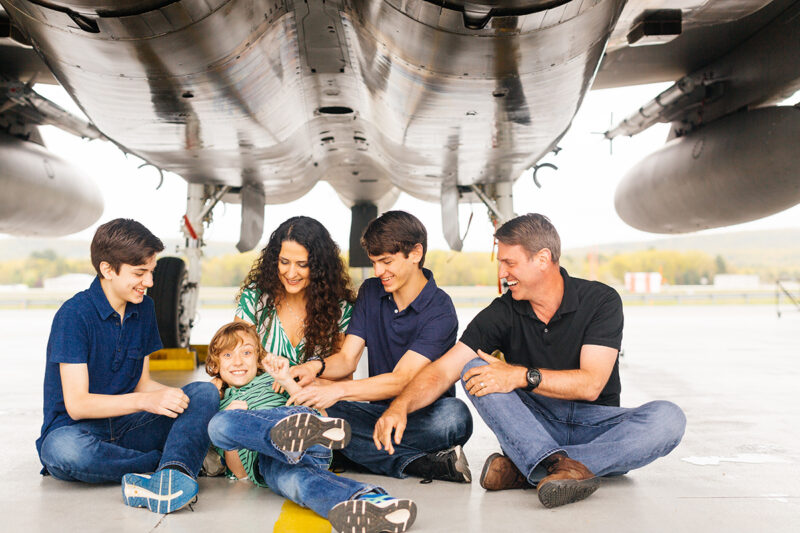 A family sits under an F-15 holding each other close tickling each other at Barnes Air National Guard Base wearing coordinated outfits for these F-15 fighter pilot family photos