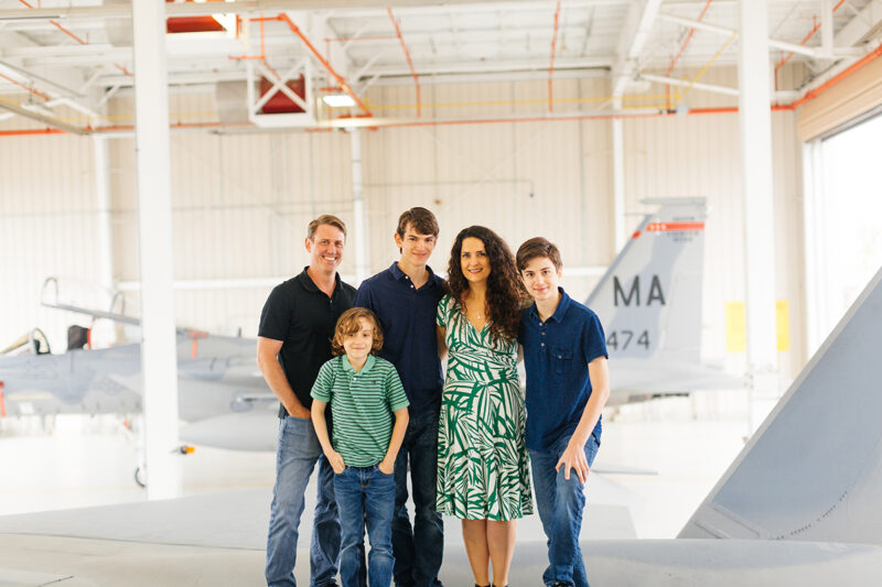 A family stands on the wing of an F-15 at Barnes Air National Guard Base wearing coordinated outfits for these F-15 fighter pilot family photos