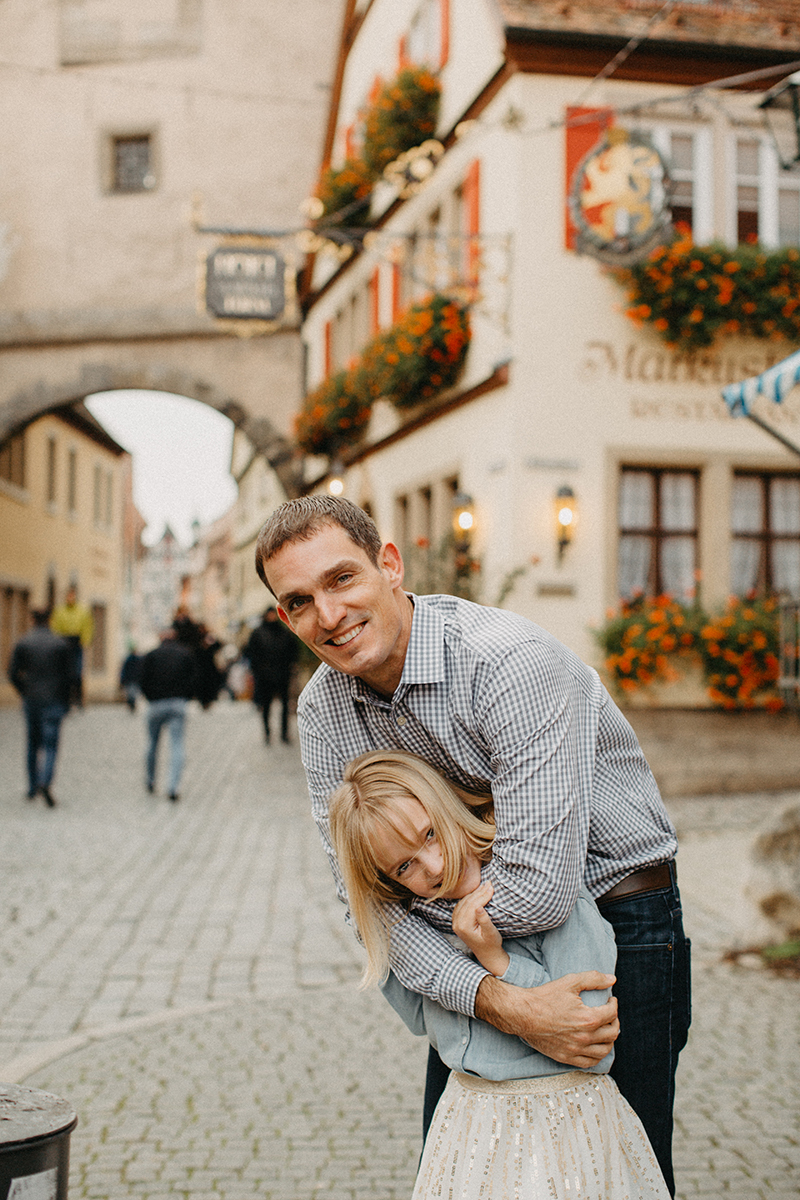 A father holds his daughter on his shoulders in Germany wearing coordinated outfits for a Rothenburg ob der Tauber family photography session