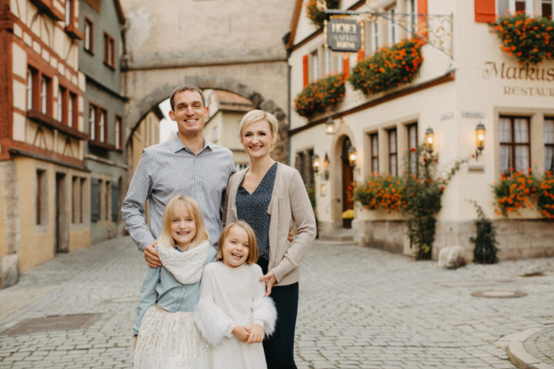 A family poses together smiling in Germany wearing coordinated outfits for a Rothenburg ob der Tauber family photography session