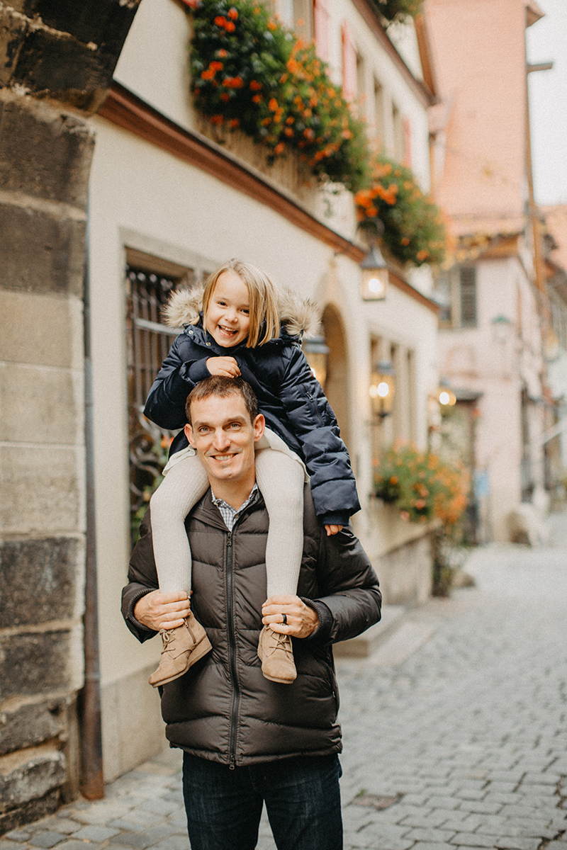 A father carries his daughter on his shoulders in Germany wearing coordinated outfits for a Rothenburg ob der Tauber family photography session