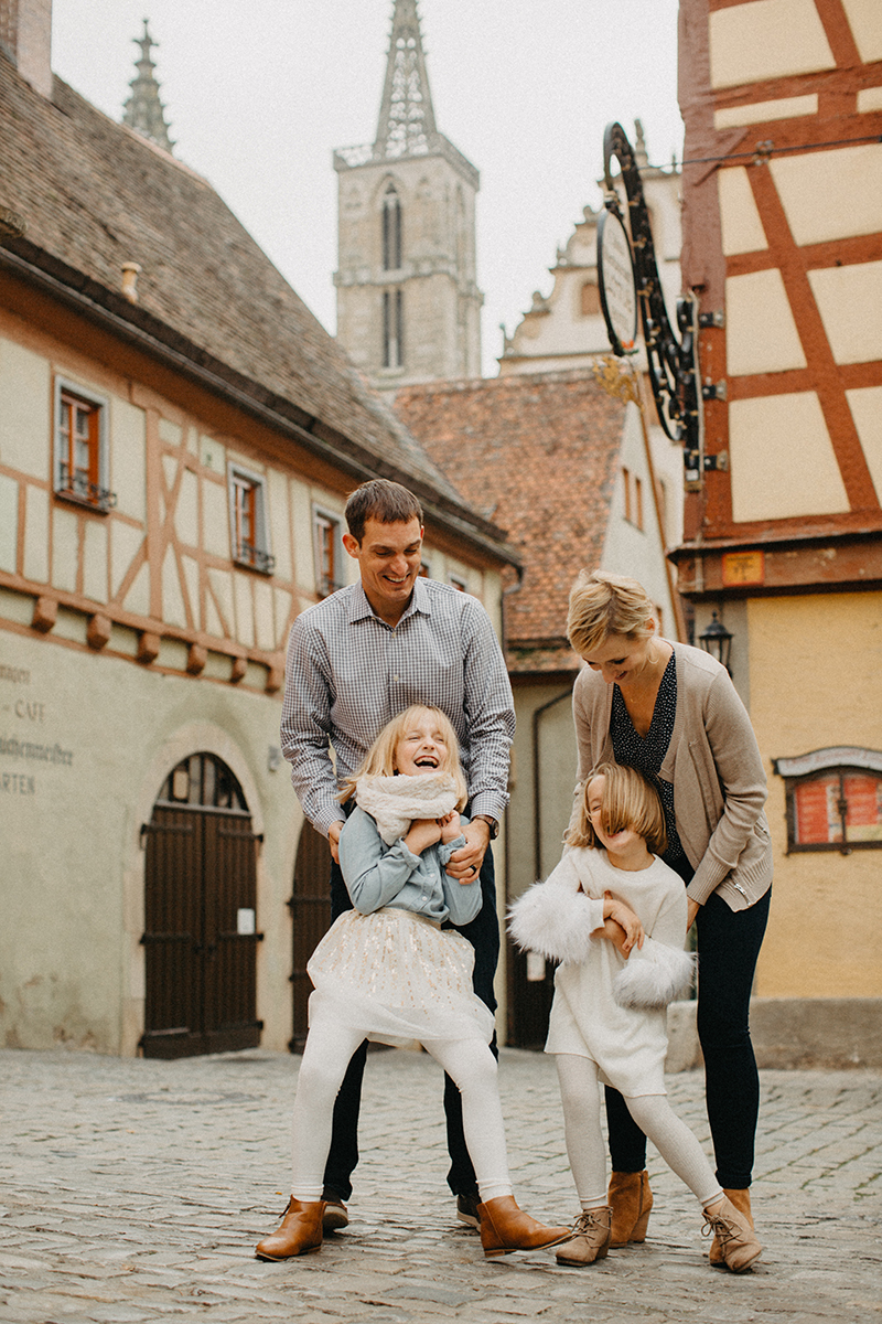 A family poses together laughing during a tickle fight in Germany wearing coordinated outfits for a Rothenburg ob der Tauber family photography session