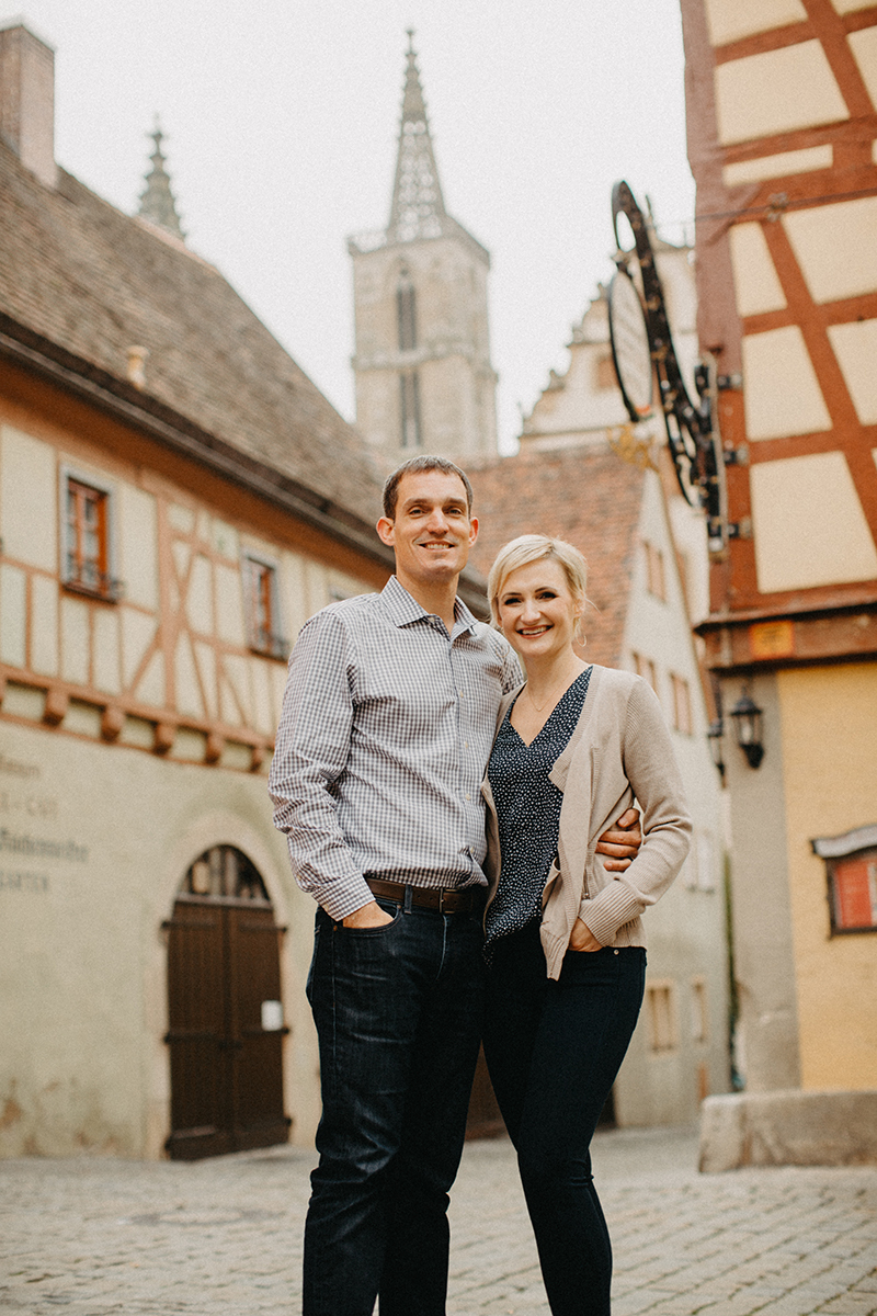 A couple hold one another in Germany wearing coordinated outfits for a Rothenburg ob der Tauber family photography session