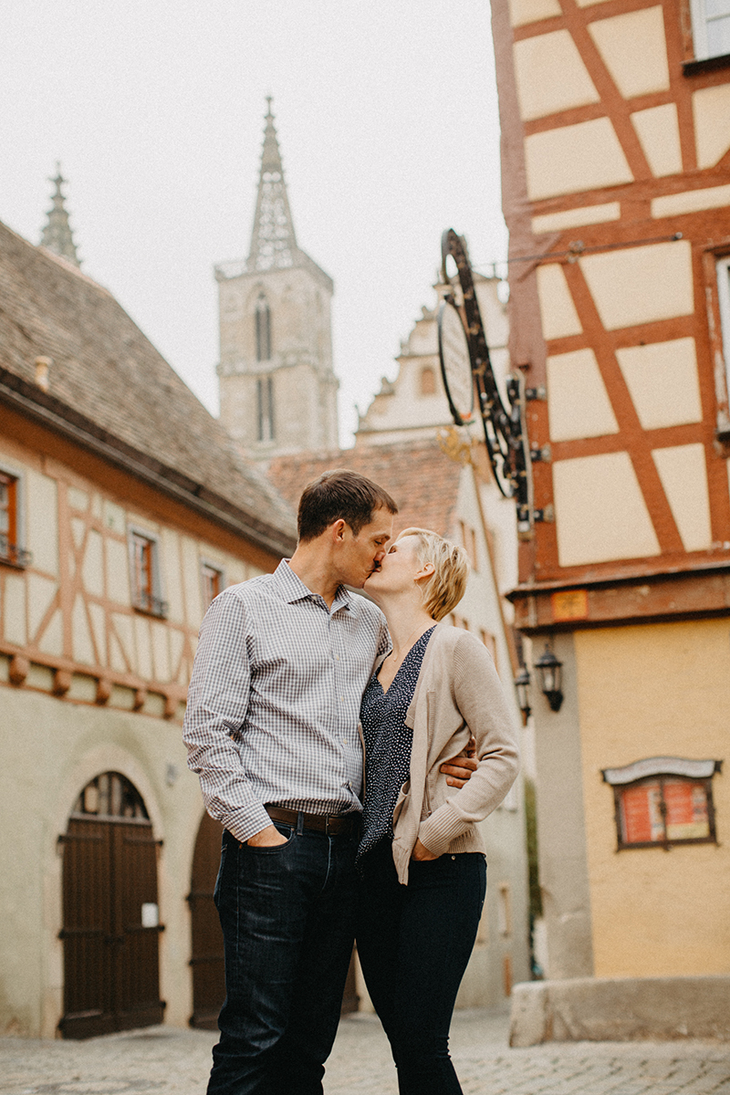 A couple hold one another and kiss in Germany wearing coordinated outfits for a Rothenburg ob der Tauber family photography session