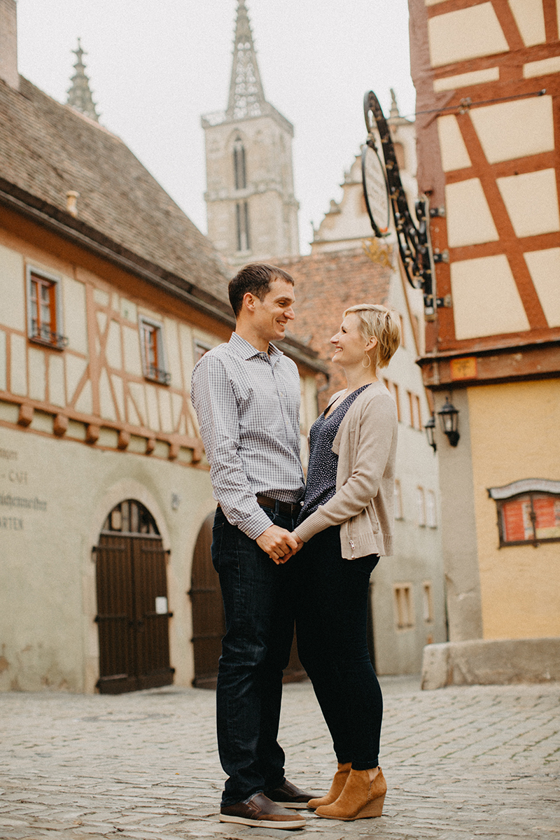 A couple hold hands and smile at one another in Germany wearing coordinated outfits for a Rothenburg ob der Tauber family photography session