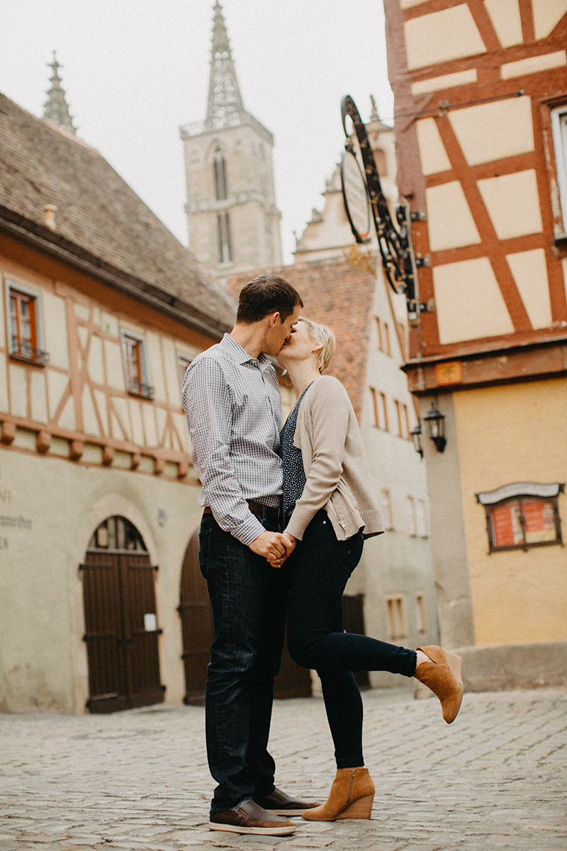 A couple hold hands and kiss in Germany wearing coordinated outfits for a Rothenburg ob der Tauber family photography session