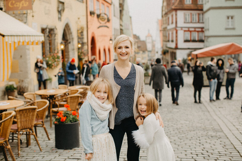 A mother walks with her daughters in Germany wearing coordinated outfits for a Rothenburg ob der Tauber family photography session