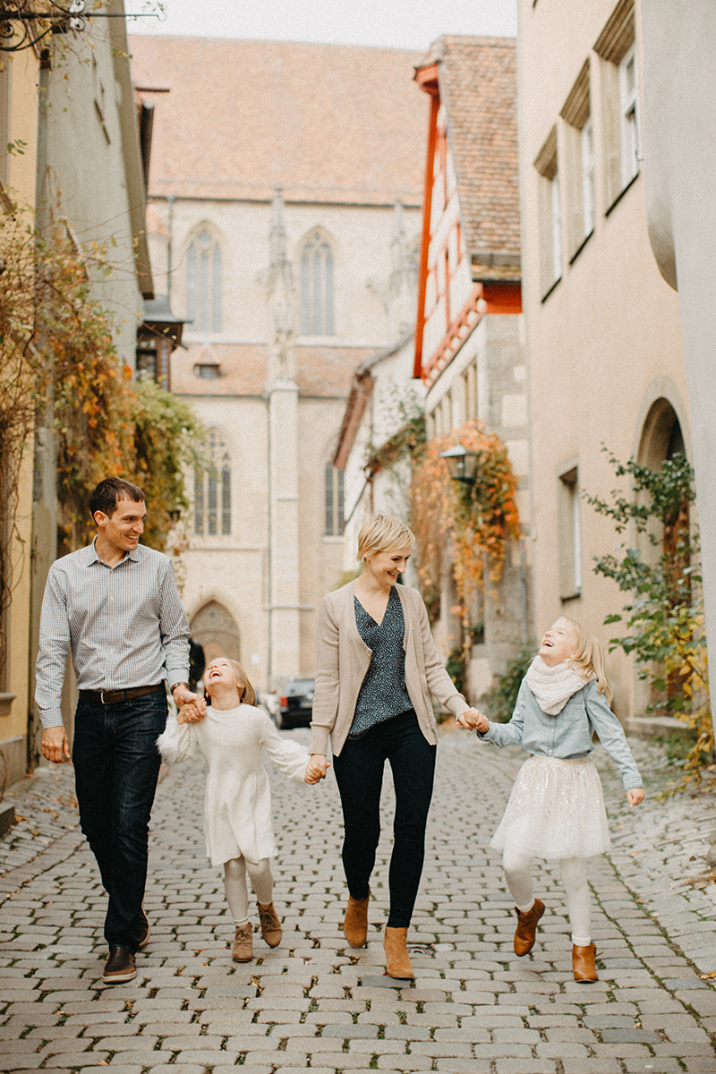 A family walks together holding hands in Germany wearing coordinated outfits for a Rothenburg ob der Tauber family photography session