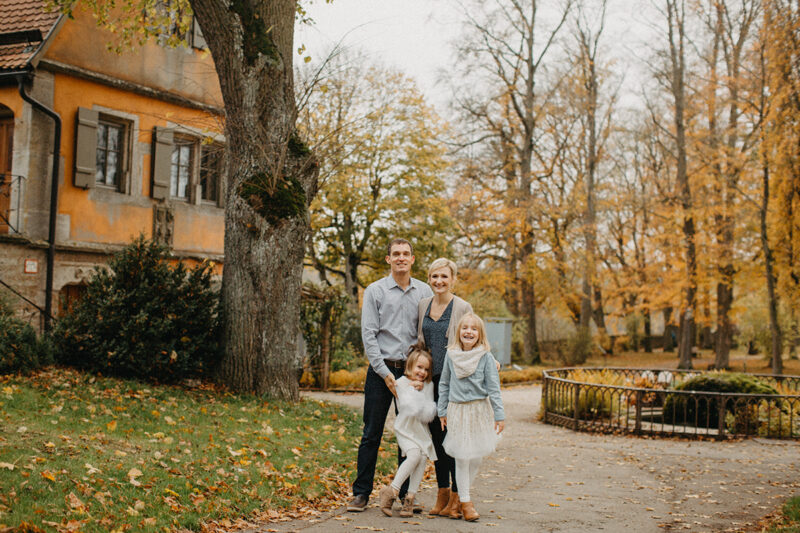 A family stands together in Germany wearing coordinated outfits for a Rothenburg ob der Tauber family photography session