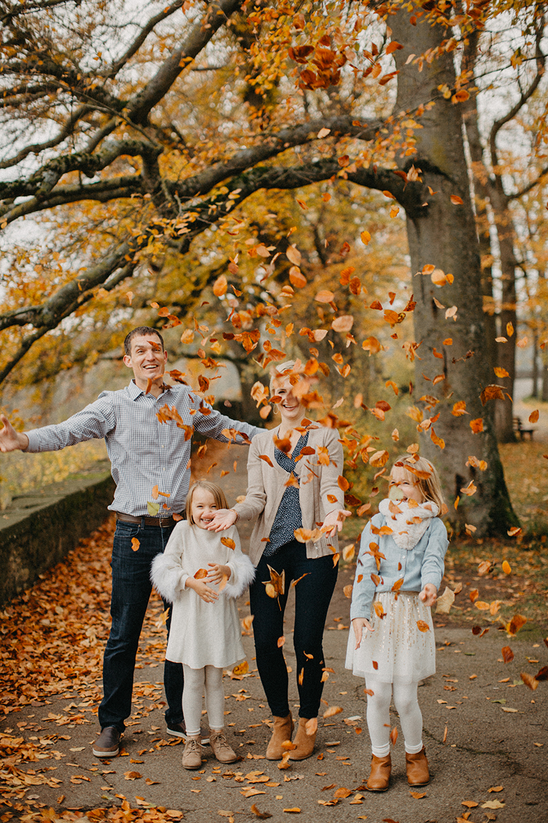 A family throws leaves together in Germany wearing coordinated outfits for a Rothenburg ob der Tauber family photography session