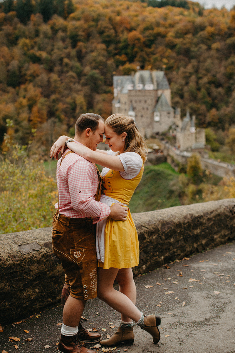 A couple hold one another on the road to Burg Eltz wearing a traditional dirndl and lederhosen for these Eltz Castle couples photos in Germany