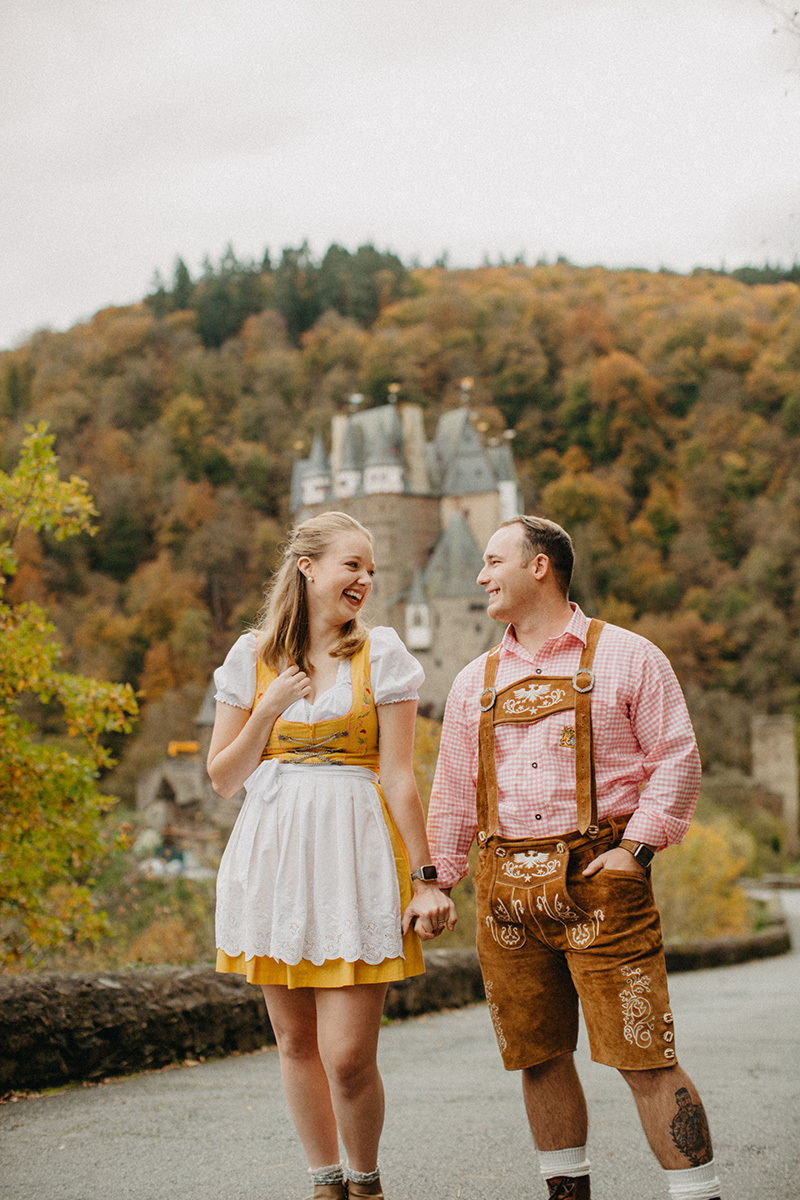 A couple hold hands on the road to Burg Eltz wearing a traditional dirndl and lederhosen for these Eltz Castle couples photos in Germany