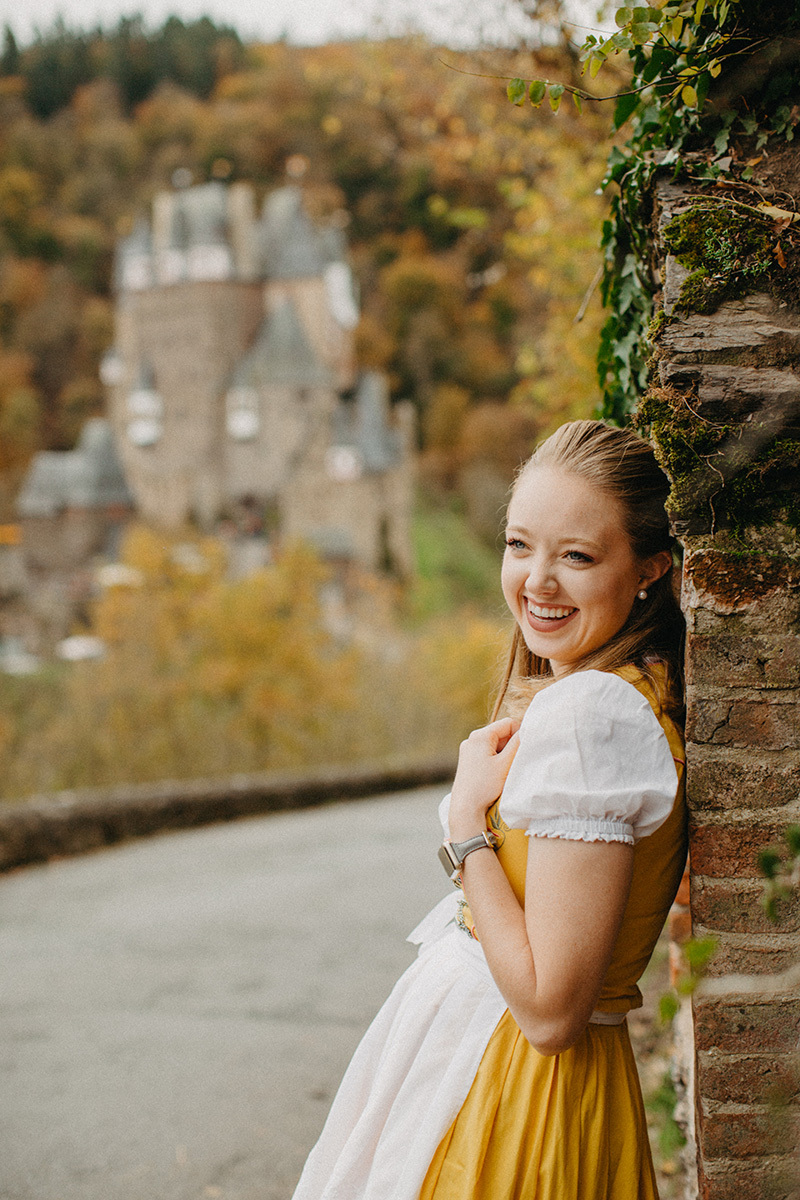 A beautiful young blonde woman poses on the road to Burg Eltz wearing a traditional dirndl for these Eltz Castle couples photos in Germany