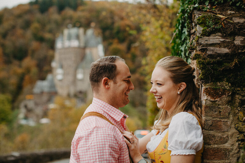 A couple embrace on the road to Burg Eltz wearing a traditional dirndl and lederhosen for these Eltz Castle couples photos in Germany