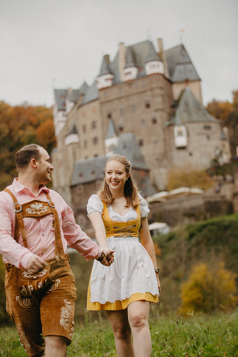 A couple walk together holding hands in a field near Burg Eltz wearing a traditional dirndl and lederhosen for these Eltz Castle couples photos in Germany